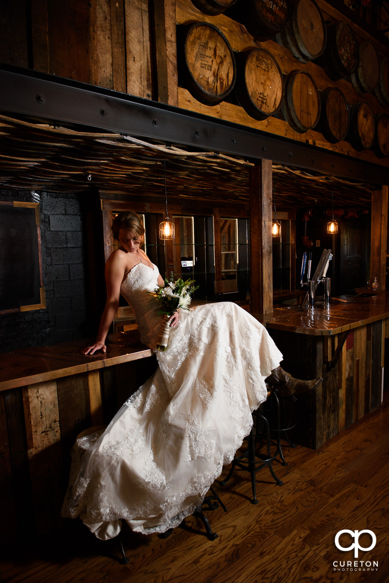 Bride sitting on the bar at Revel Event Center during her bridal session.