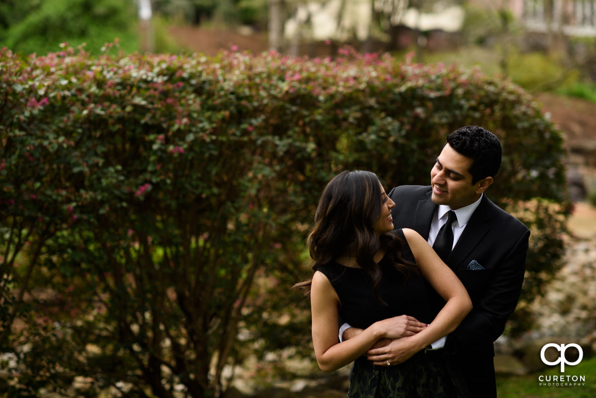 Man sneaking up on his fiancee at their engagement session at The Rock Quarry Garden and Cleveland Park in Greenville,SC.