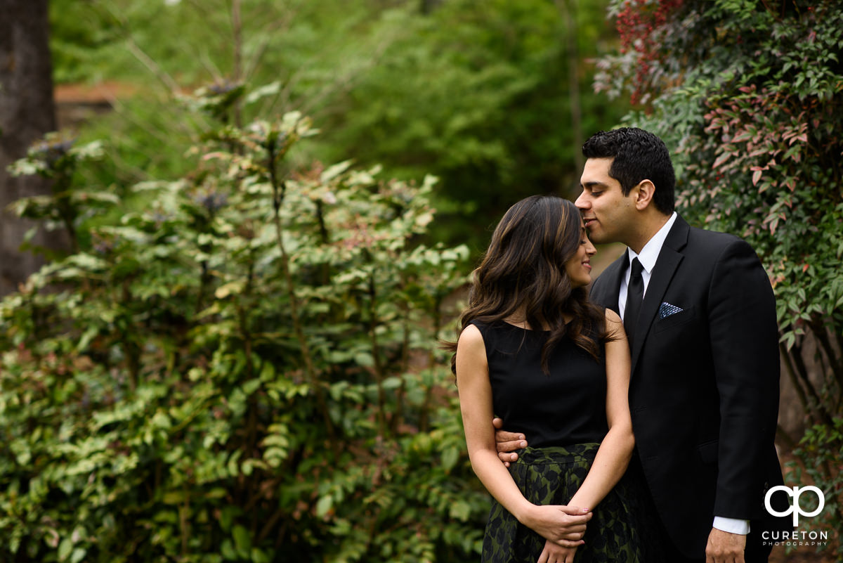 Groom kissing his bride on the forehead at their engagement session at The Rock Quarry Garden and Cleveland Park in Greenville,SC.