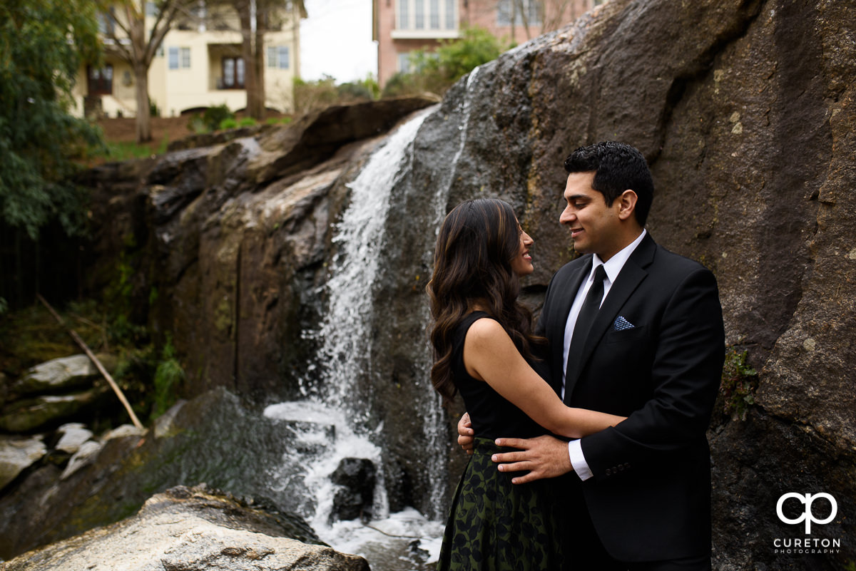 Nicely dressed couple dancing near a waterfall at their engagement session at The Rock Quarry Garden and Cleveland Park in Greenville,SC.