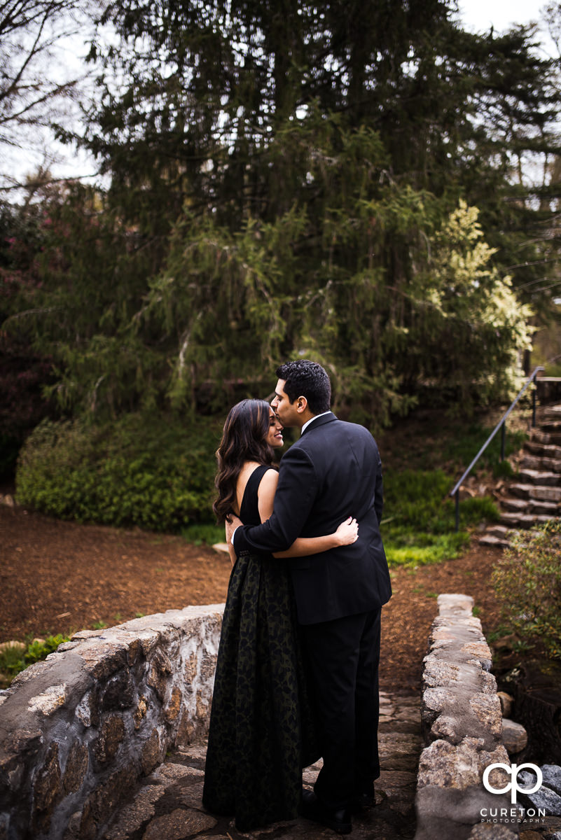 Man kissing his fiancee on a bridge at The Rock Quarry Garden in Greenville.