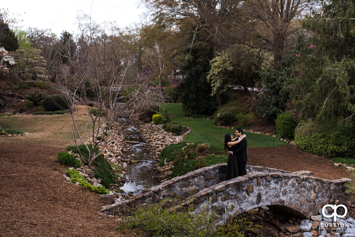 Engaged couple dancing on a stone bridge in The Rock Quarry Garden in Greenville.