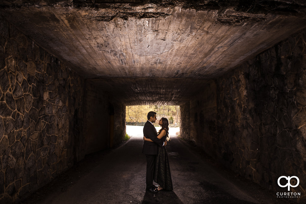 Engaged couple dancing underneath a bridge in Cleveland Park in Greenville,SC.