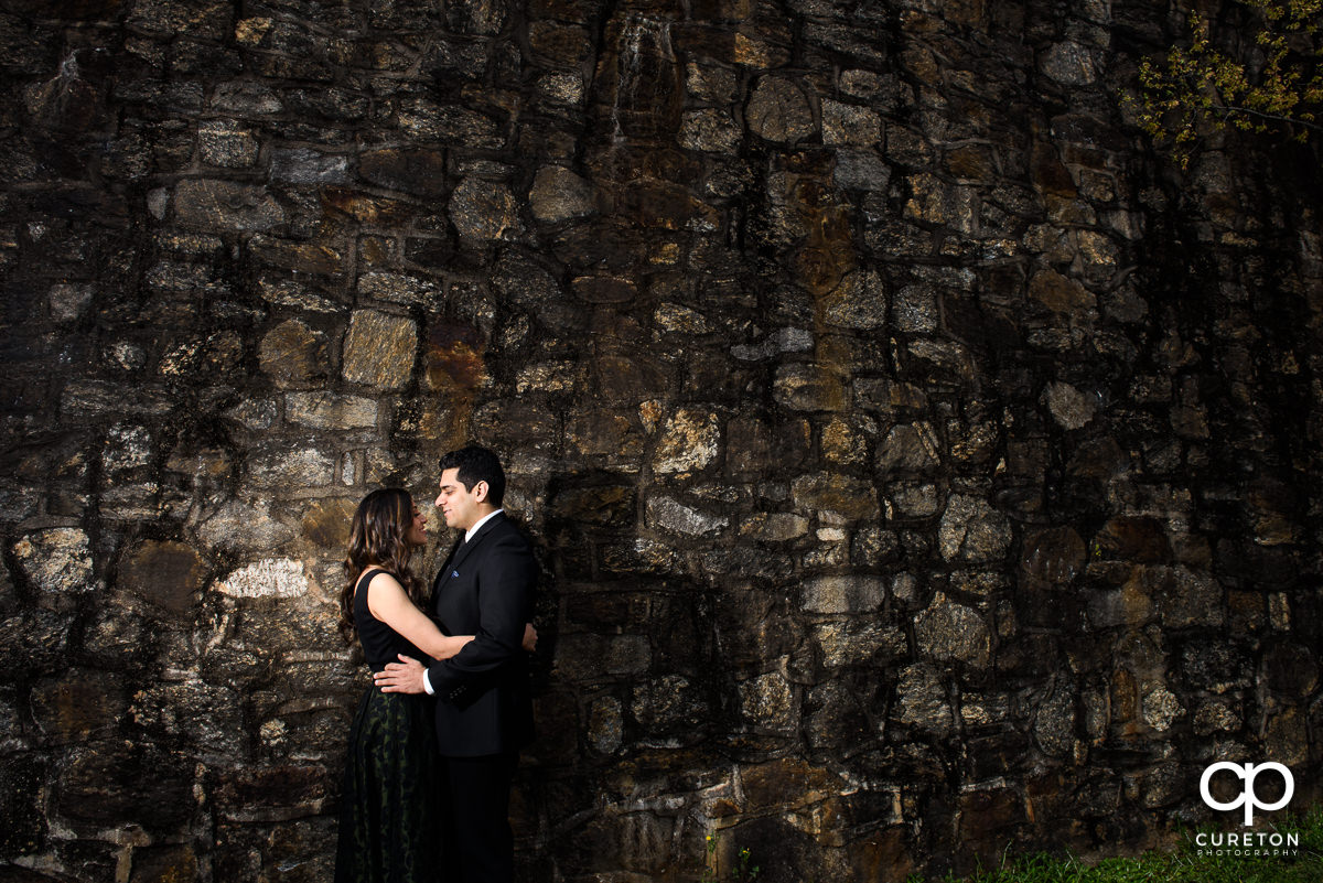 Happy couple smiling at each other next to a stone wall at their engagement session at The Rock Quarry Garden and Cleveland Park in Greenville,SC.