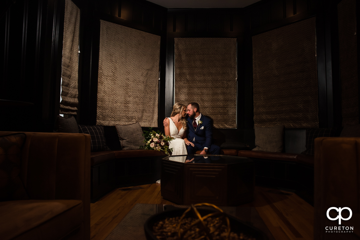 Bride and groom sitting in a dark room before their Rocky River Plantation wedding in Anderson,SC.