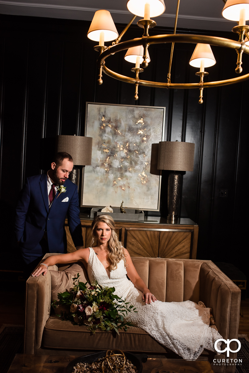Bride and groom sitting on a couch in a black room their Rocky River Plantation wedding in Anderson,SC.