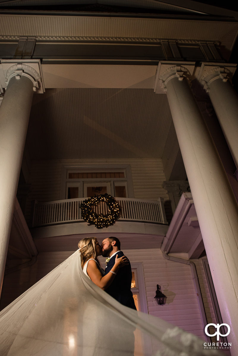 Bride and groom kissing on the front porch of an antebellum style house at their Rocky River Plantation wedding in Anderson,SC.