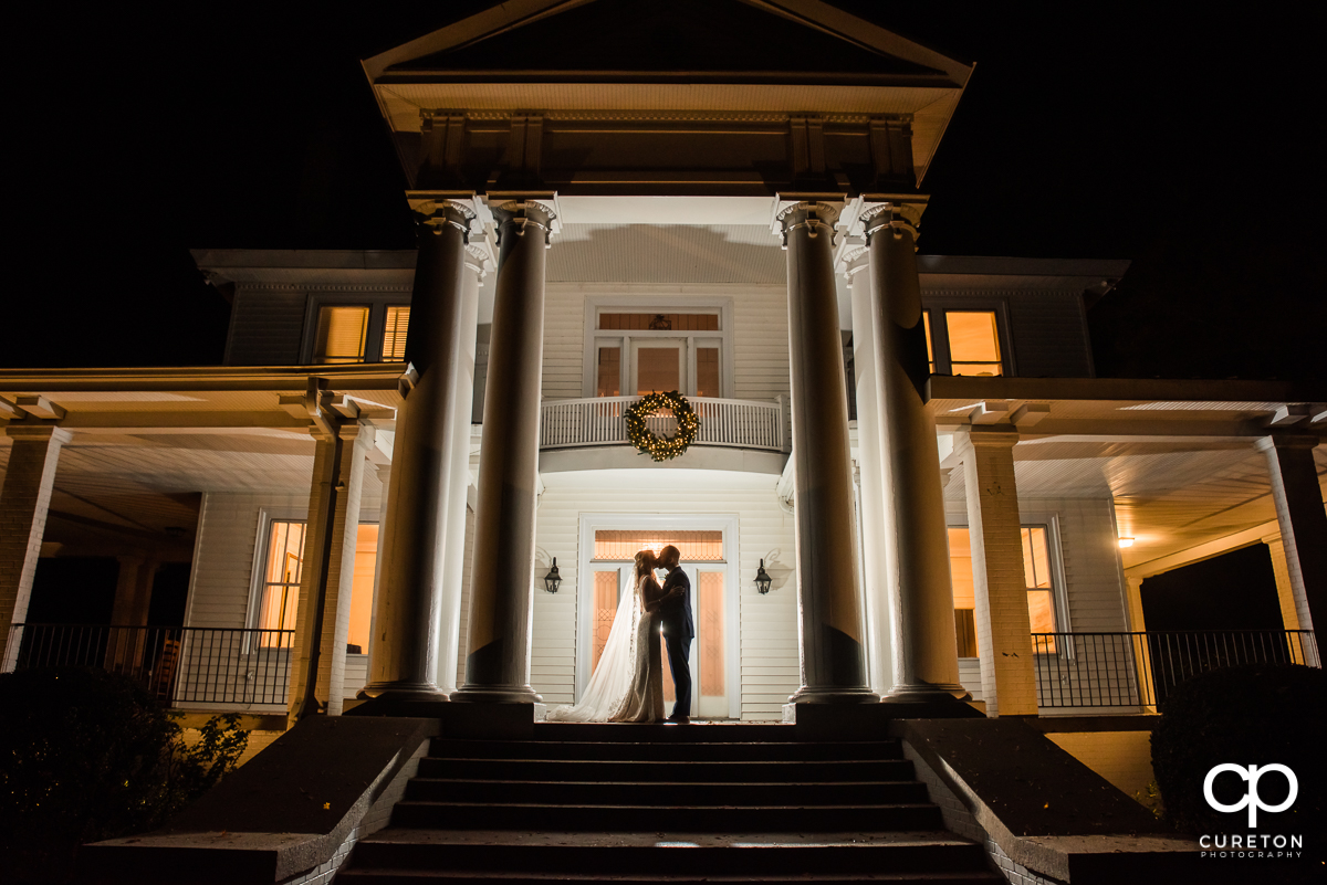 Groom kissing his bride on the front porch of a huge home at their Rocky River Plantation wedding in Anderson,SC.