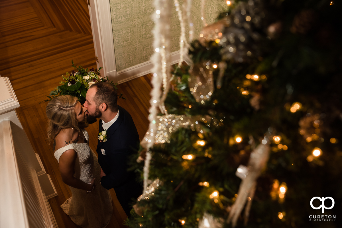 Bride and groom kissing in front of a lit Christmas tree at their Rocky River Plantation wedding in Anderson,SC.