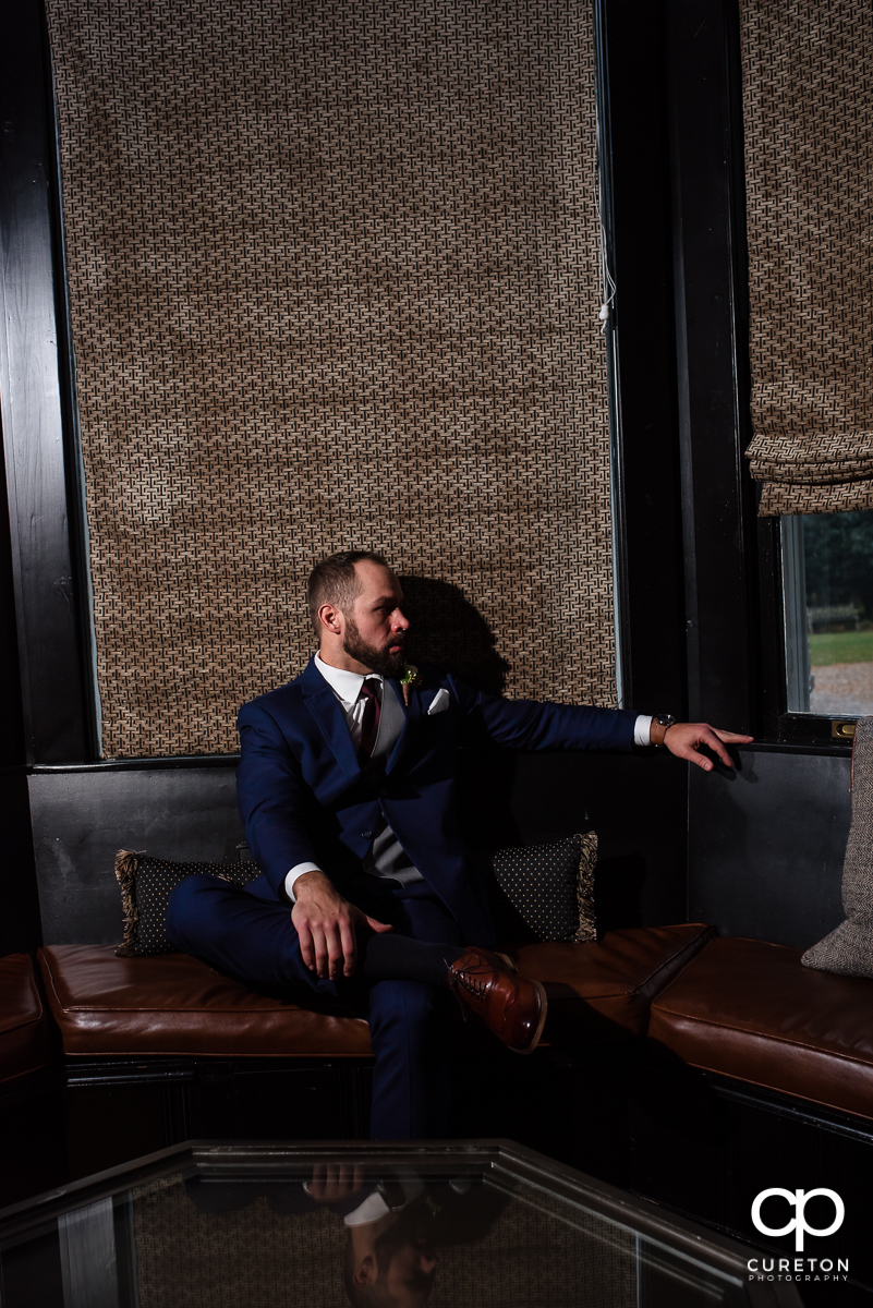 Groom sitting on the couch.