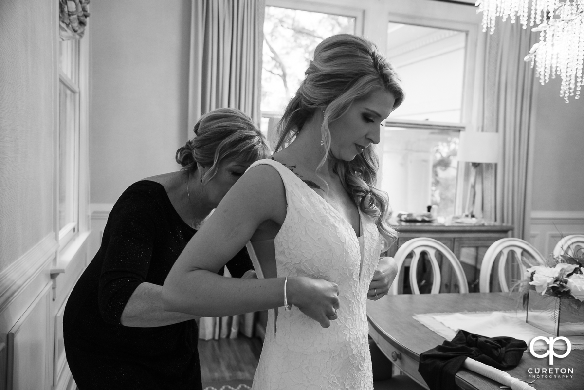 Bride being helped into her dress.