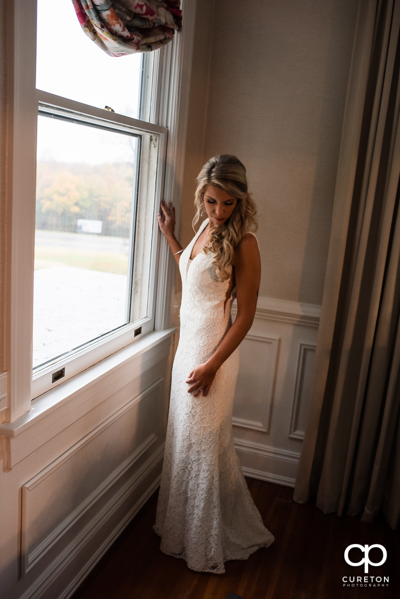 Bride standing in front of a window.