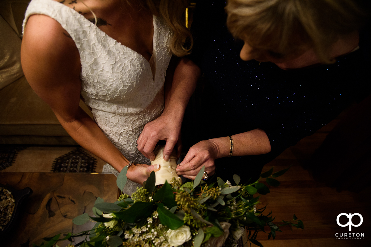 Bride and her mother fixing her flowers.