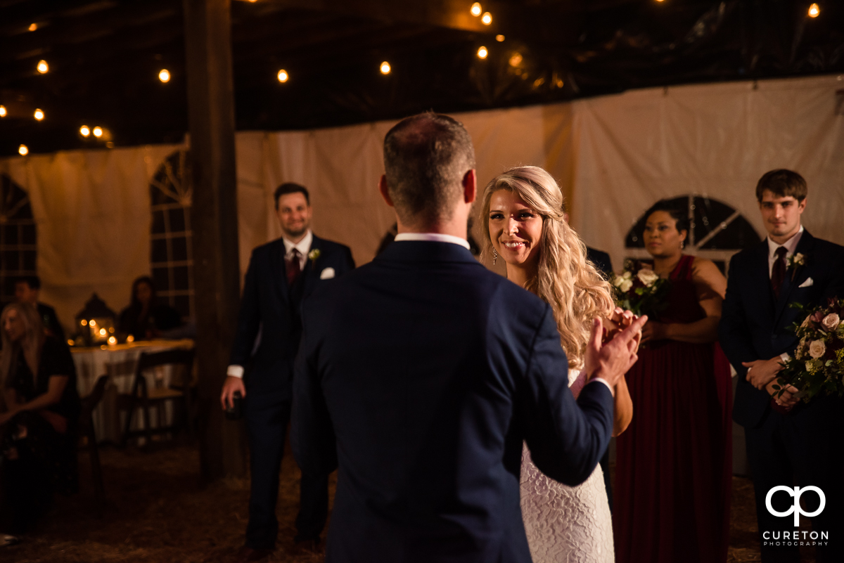 Bride smiling at her groom during their first dance at the Rocky River plantation wedding reception.