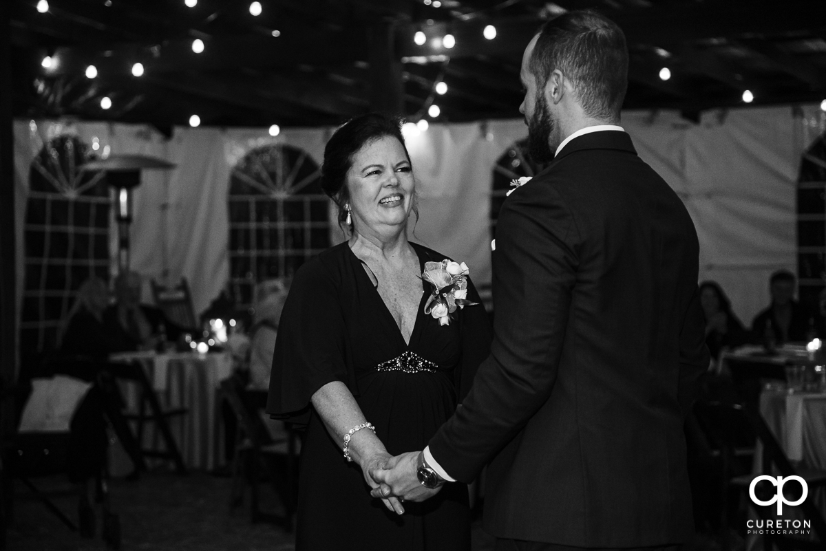 Groom's mom smiling at him as they share a dance at the reception.