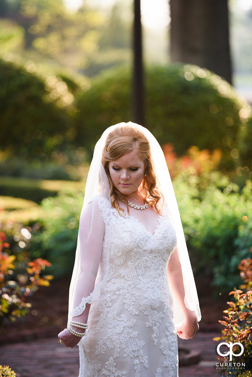 Bride holding her veil in the rose garden at Furman,.