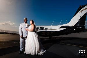 Newly married couple standing beside and airplane at the downtown airport in Greenville,SC.