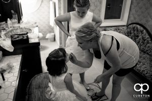 Bride putting make up on the flower girl.