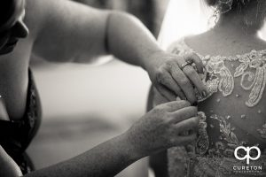 The bride being helped into her dress.