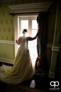 The bride looking out the window of the bridal suite at the Ryan Nicholas Inn.