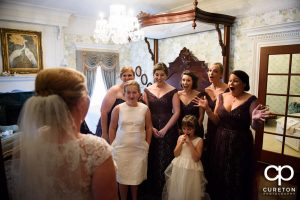 The bride being revealed to the bridesmaids for the first time.