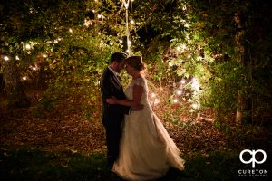 Bride and groom standing in a forest full of twinkly lights.
