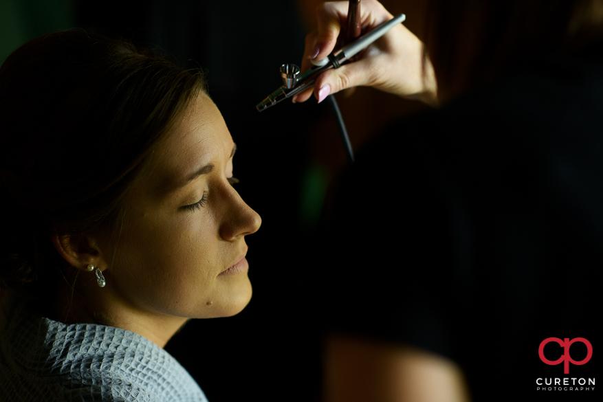 Bride having airbrushed makeup applied.