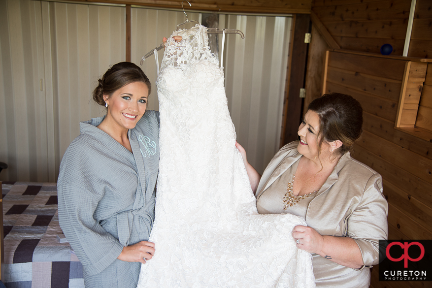 Bride and mother looking at her dress.