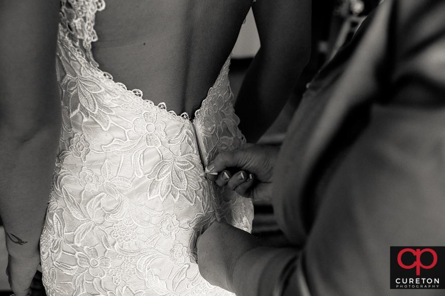 Bride's mom zipping up her dress.