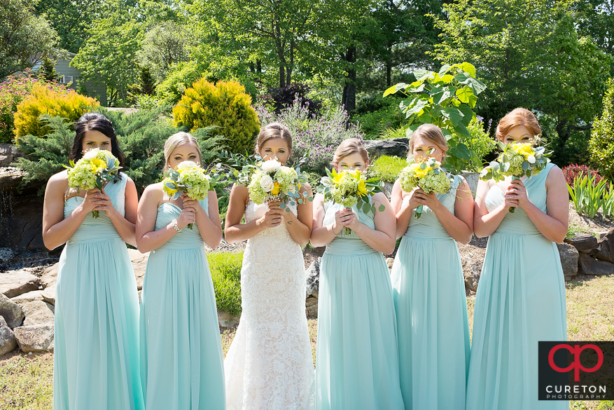Bride and bridesmaids holding thier flowers up.