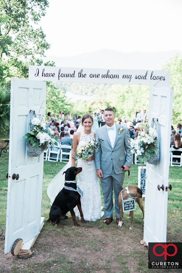 Bride and groom walk back down the aisle with their dogs.