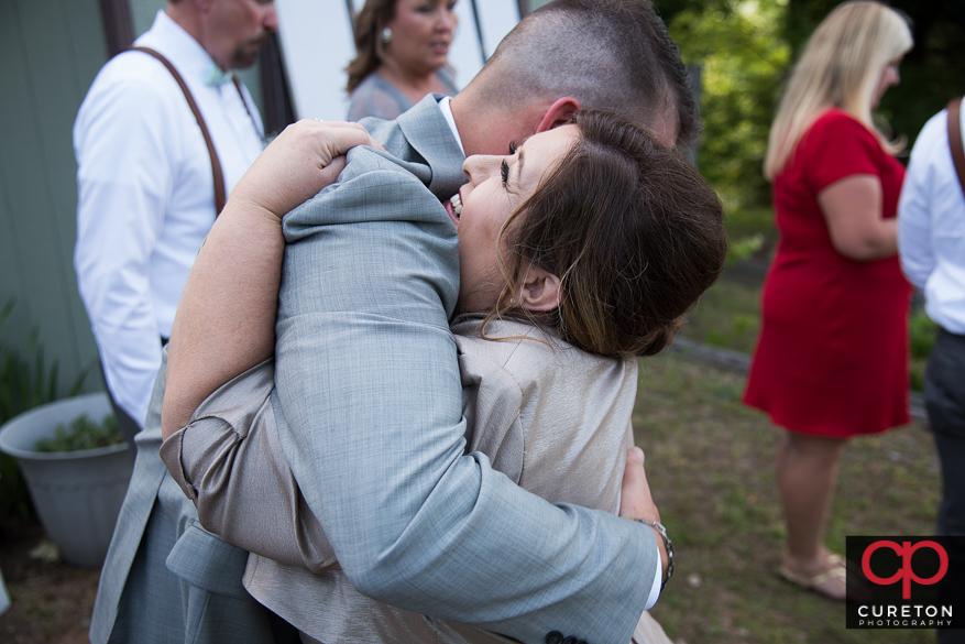 Mother of bride hugging the groom.