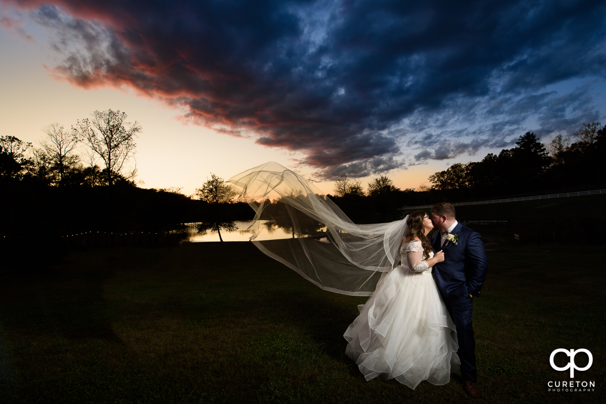 Groom kissing his bride at sunset as her veil blows in the wind at their South Wind Ranch wedding.