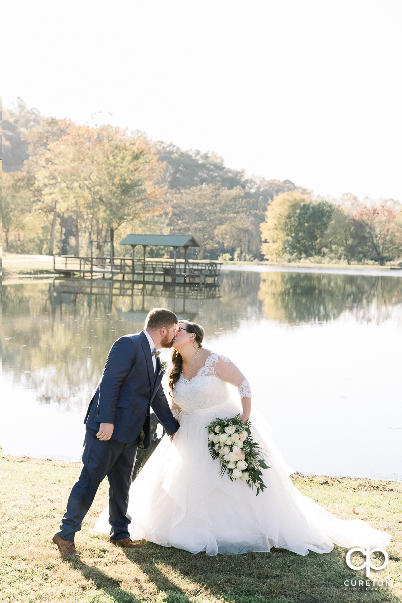 Bride and groom kissing in front of the lake at South Wind Ranch in Travelers Rest, SC on their wedding day.
