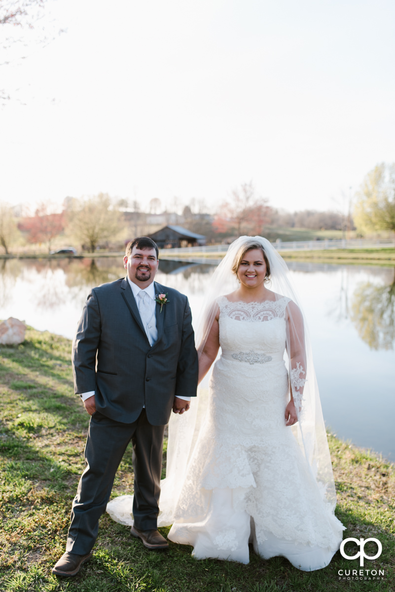 Bride and groom holding hands for a stroll by the lake during their South Wind Ranch wedding in Travelers Rest,SC.