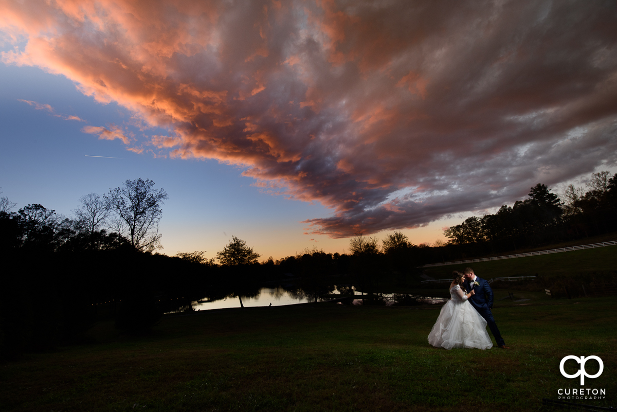 Bride and groom dancing underneath an amazing sky at sunset at their South Wind Ranch wedding in Travelers Rest SC.