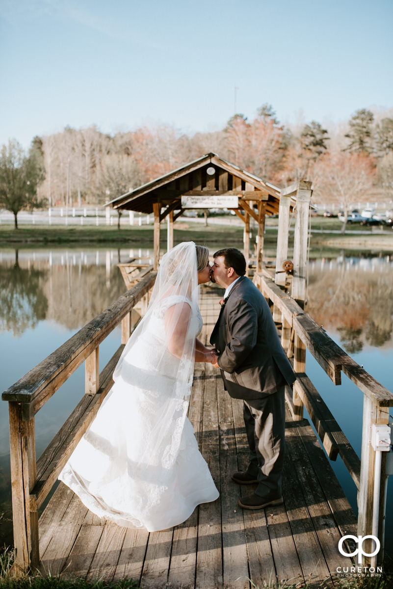Married couple kissing by the lake at South Wind Ranch.