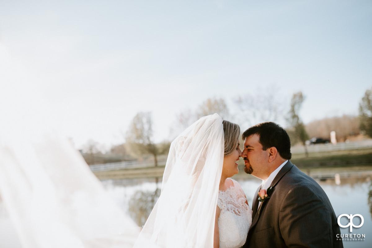 Groom eskimo kissing with his bride.
