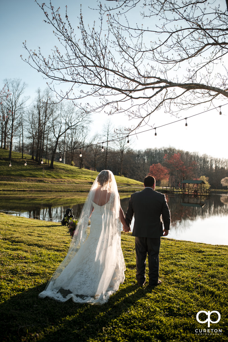 Bride and groom looking at the lake at South Wind Ranch.