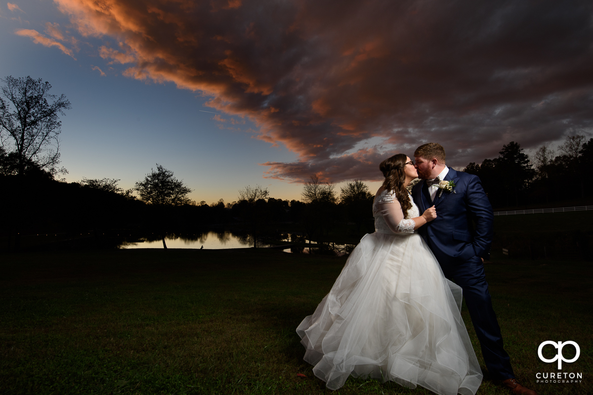 Groom kissing his bride at sunset at their Travelers Rest wedding.