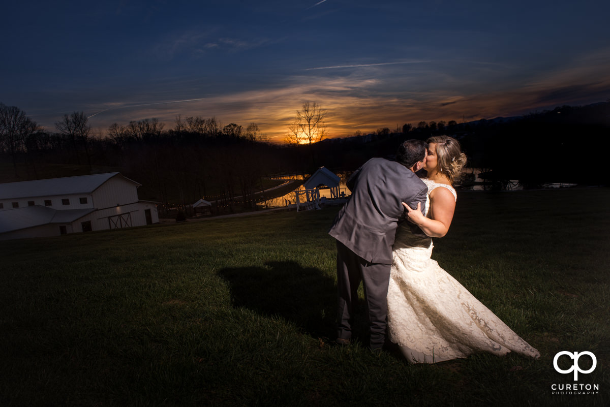 Groom dipping his bride at sunset during their South Wind Ranch wedding in Travelers Rest,SC.