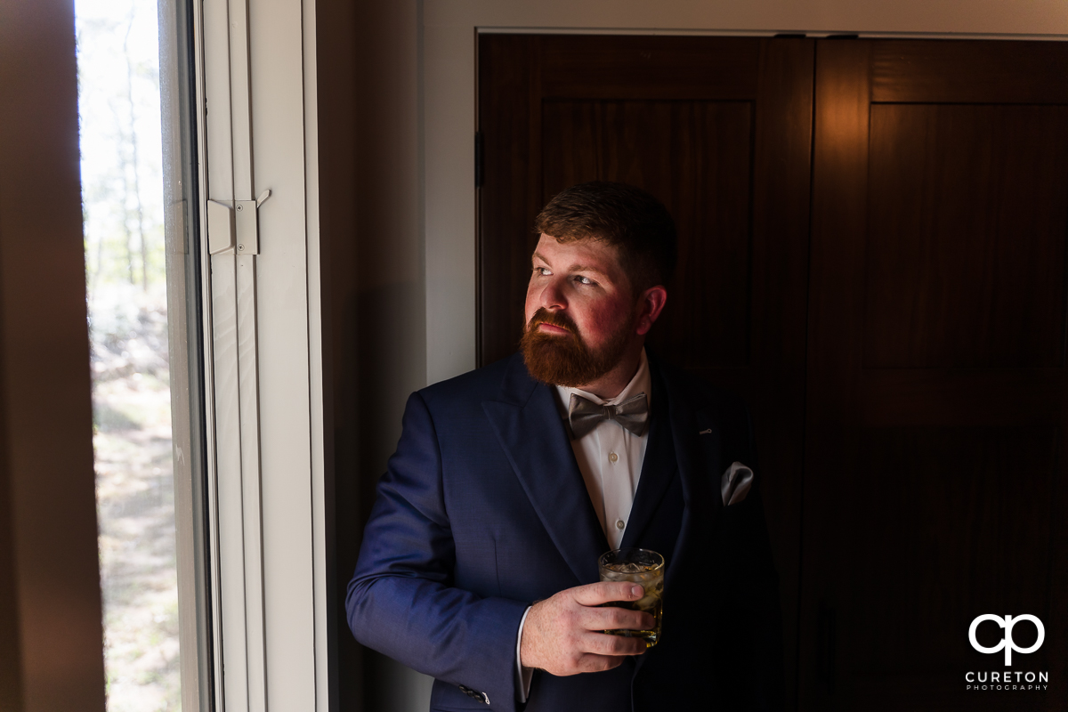 Groom holding a mixed drink looking out the window before his wedding.
