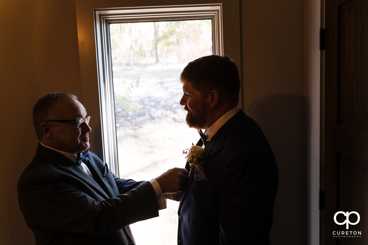 Bride's father helping the groom get ready for the wedding.
