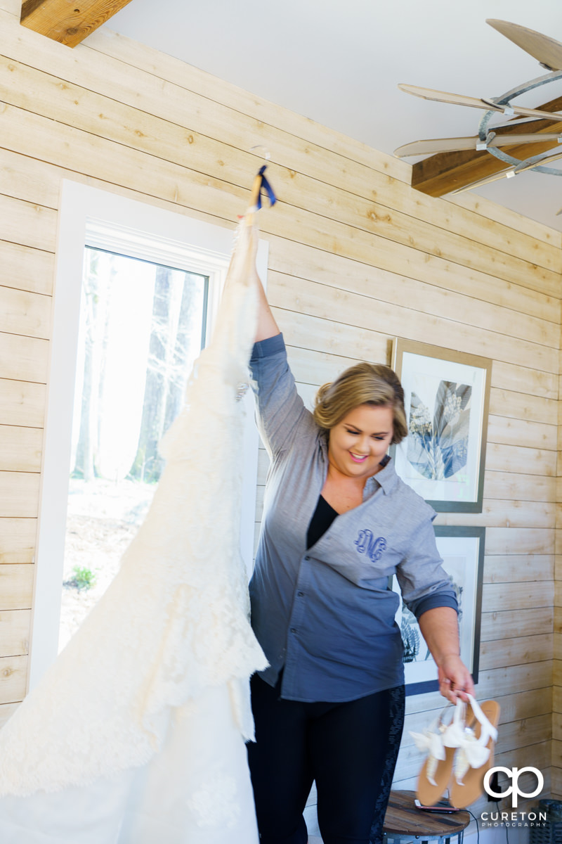 Bride holding her dress inside the bridal suite at South Wind Ranch