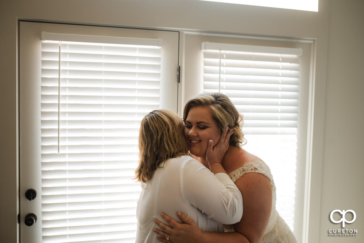 Mother of the groom kissing the bride on the cheek.