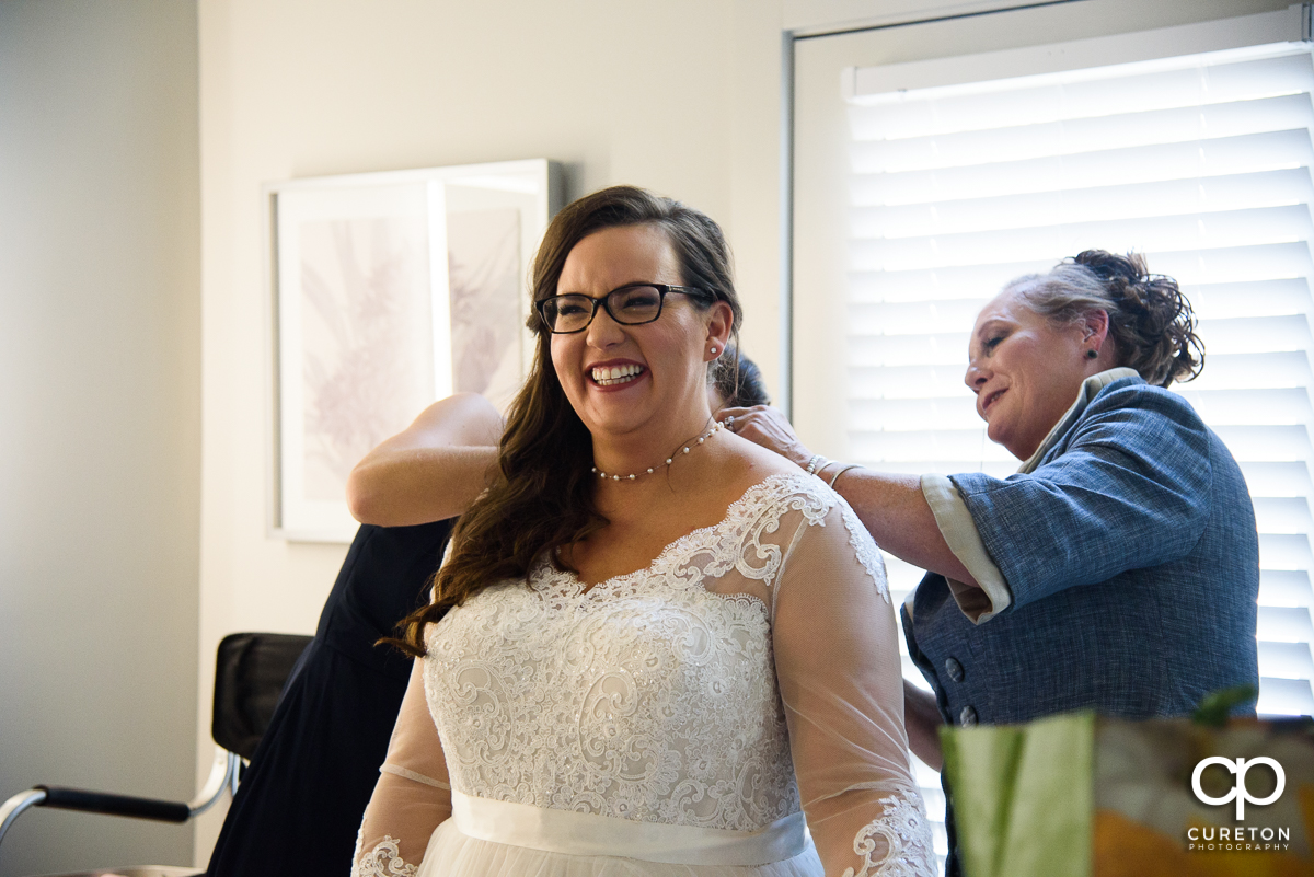 Bride laughing as she gets ready for her wedding.
