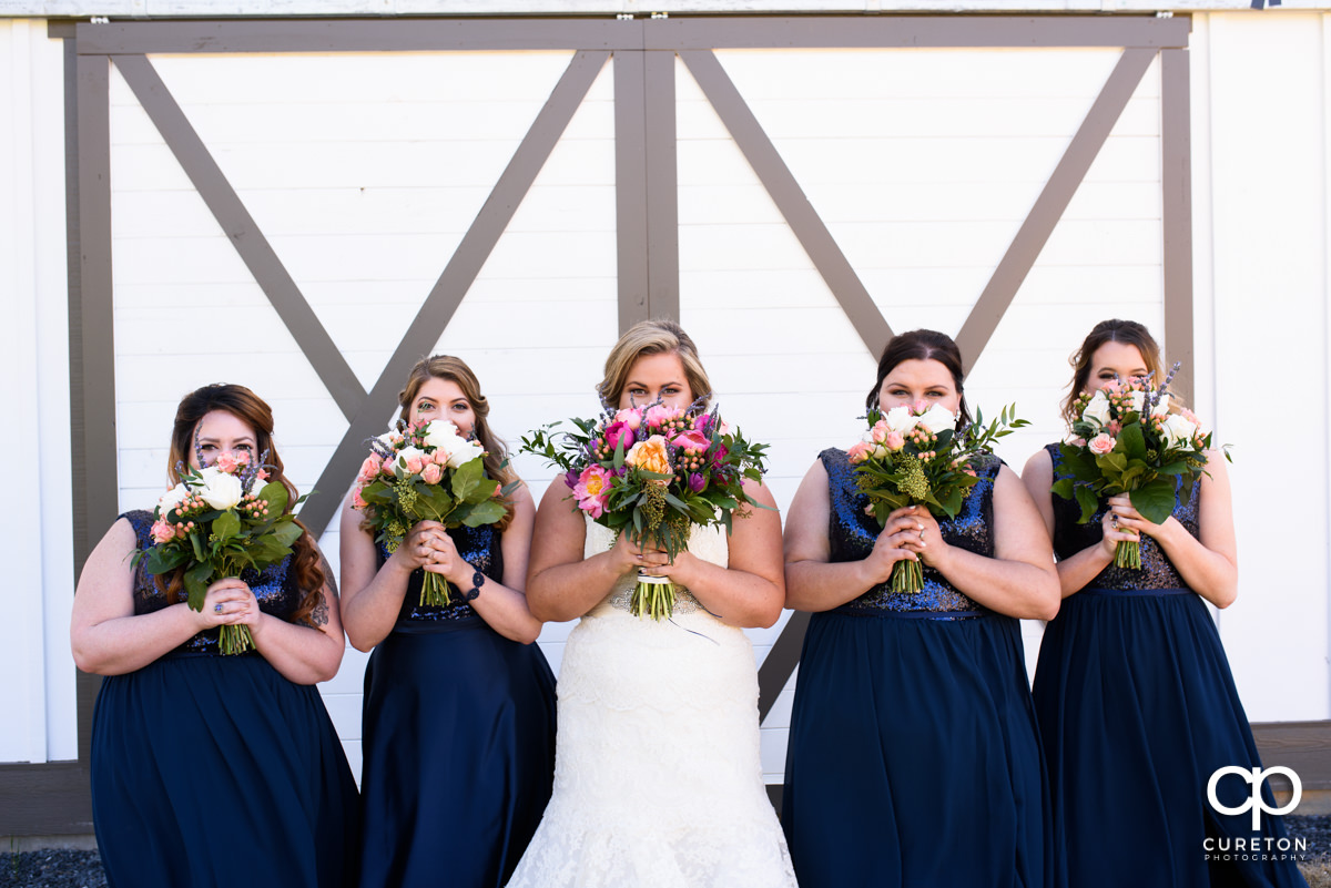 Bride and bridesmaid holding flowers over their faces at South Wind Ranch