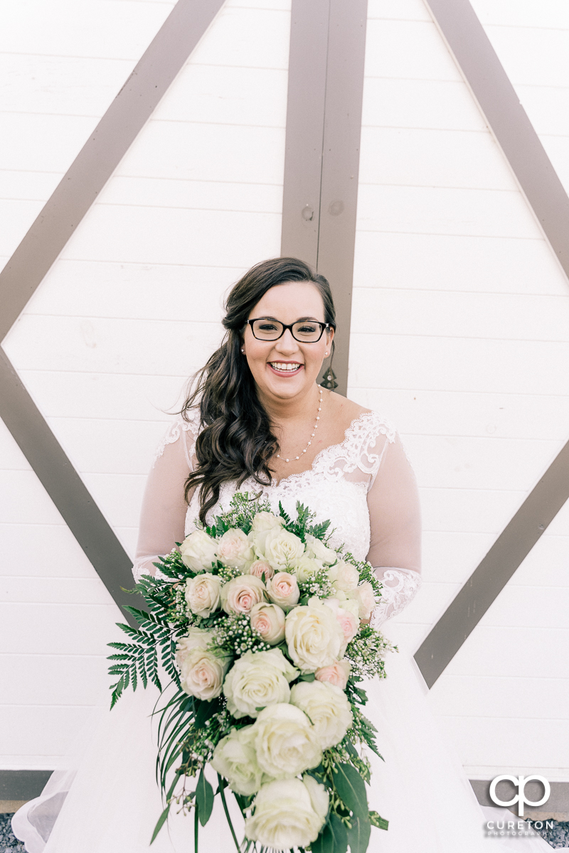 Bride holding her bouquet in front of the white barn doors at South Wind Ranch.