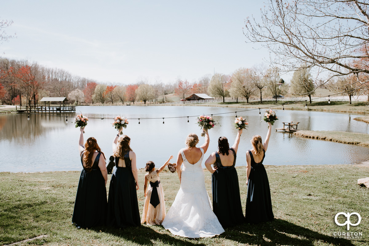 Bride and bridesmaid holding their flowers in the air by the lake at South Wind Ranch.