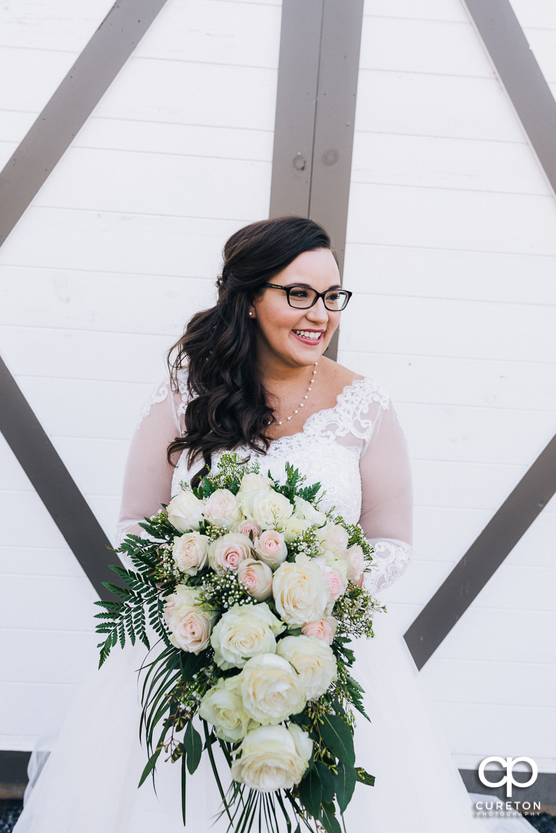 Bride smiling with her flowers in front of a white barn.